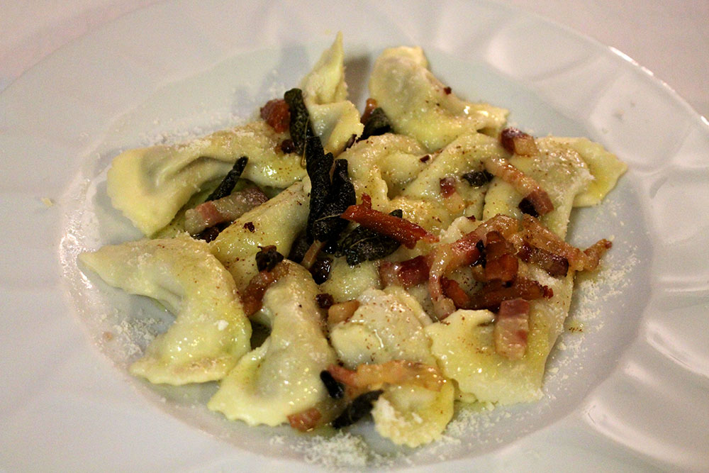 Home-made Casoncelli (ravioli) Bergamo style (dressed with Grana Padano cheese, sage, bacon and butter)